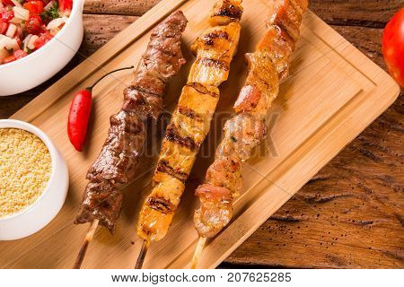 Assorted Steak Skewers On Top Of A Board
