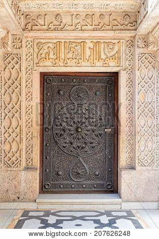 Closed wooden aged door with ornate bronzed floral patterns at the mosque of The Manial Palace of Prince Mohammed Ali Tewfik Cairo Egypt