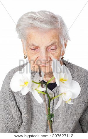 Elderly female with dementia disease holding a white orchid on isolated background