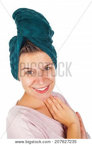 Attractive young woman with bath towe on head applying facial moisturizer