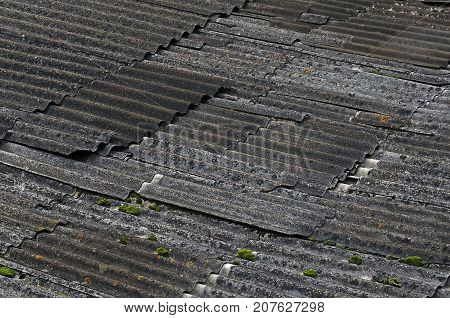 Old destroyed asbestos roof in the dark weather