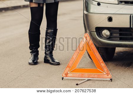 Auto assistance and insurance troubles while traveling concept. Broken car and auto triangle on road woman waiting for help.