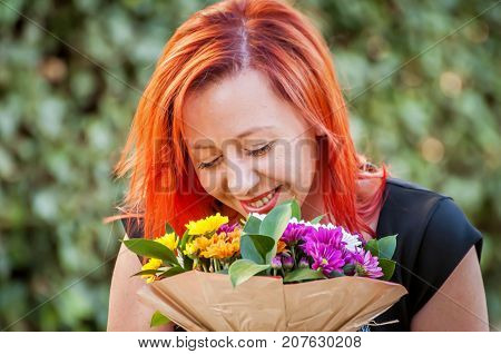 A portrait of an elegant young Caucasian girl with red hair smiling and holding a flower bouquet in her hands, smelling the flowers. March 8, Valentine's Day concept, first date, wedding proposal.