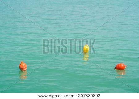 Three Bright Yellow And Orange Marker Buoys Floating In Blue Turquoise Lake Water, Balaton, Hungary.
