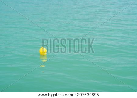 One Bright Yellow Marker Buoy Floating In Blue Turquoise Lake Water, Balaton, Hungary. Abstract Comp