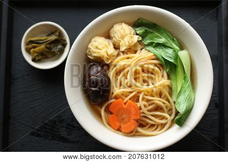 Chinese yellow lomein noodles soup with carrots mushroom and wonton and vegetable poster