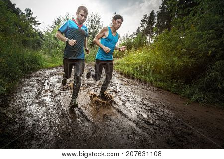 Two athletic sporty men run along the wild muddy rural road