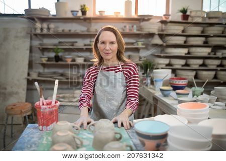 Portrait of female potter standing at worktop in pottery workshop