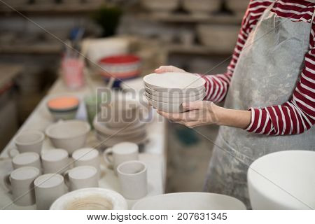 Mid section of female potter holding stack of bowls in pottery workshop