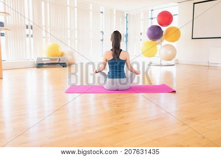 Rear view of woman performing yoga in the gym