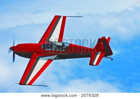 A red airplane flyies in the sky poster