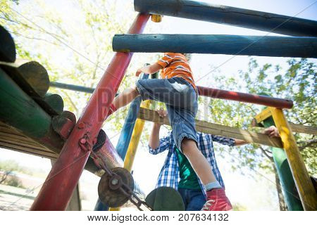 Low angle view of father standing by boy moving up on outdoor play equipment