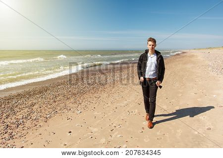 young man walking on an empty beach