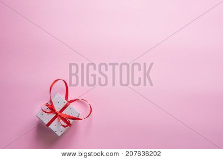 Elegant Gift Box Tied with Red Ribbon with Bow in Heart Shape on Pink Background. Valentine Wedding Mother's Day Birthday Women. Copy Space. Greeting Card Poster Template.