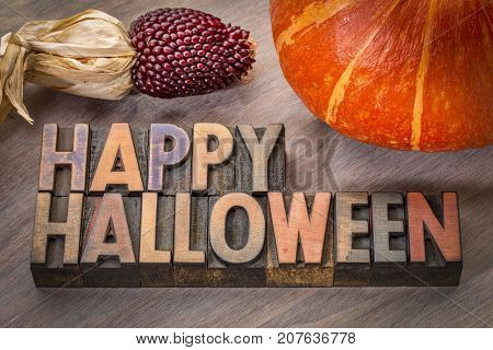 Happy Halloween greeting card - typography in vintage letterpress wood type with a pumpkin and strawberry corn
