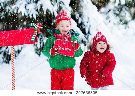 Happy children in knitted reindeer hat and scarf holding letter to Santa with Christmas presents wish list at red mail box in snow under Xmas tree in winter forest. Kids sending post to North Pole.