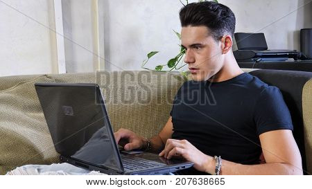 Preoccupied, worried young male worker staring at laptop computer screen at home with alarmed expression, typing frantically