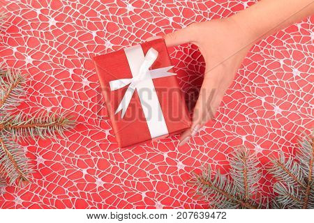 Gift box in human hands. Branch of Christmas tree, ribbons, bow, cones and a ball of brown threads lie on a red with white addition background. Cope space. Close-up of gift.
