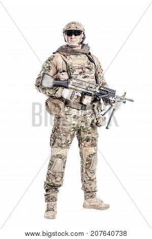 Full length low angle studio shot of big muscular soldier in field uniforms with machine gun, portrait isolated on white background lot of copyspace. Protective goggles glasses are on