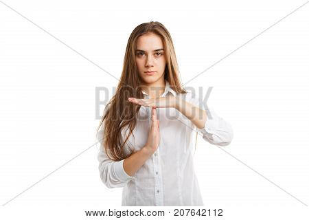 Serious and strict business-woman is showing break sign, isolated on a white background. An elegant and young lady showing timeout gesture. Timeout signal hand. Positive and negative human emotions.