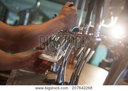 Cropped hands of bartender pouring beer from tap at bar