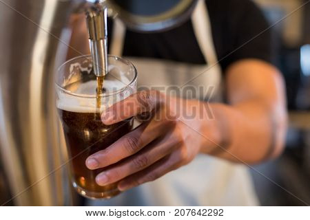 Midsection bartender pouring beer from tap at bar