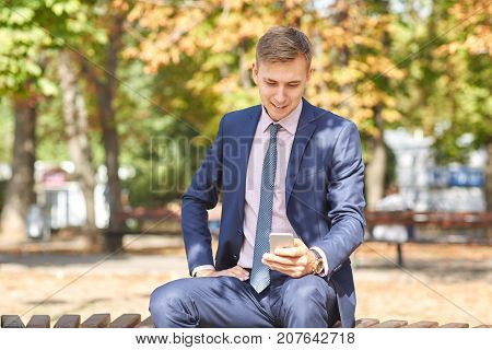 Handsome smiling man walking around the park. Siting on the bench and looking on the phone in the park on the nature background. Business concept.