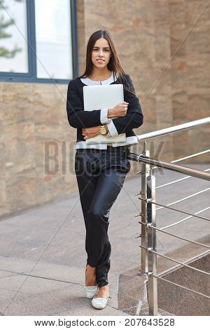Young beautiful girl holding a folder and posing at the camera in black clothes on the background of granite wall. Full lenght of woman. Business concept.