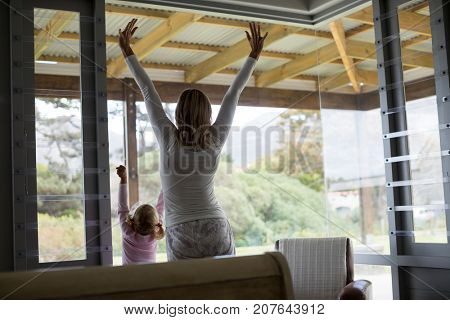 Rear view of mother and daughter standing together at home