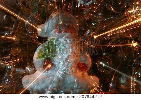 Abstract Santa Ornament on Christmas Tree with Light Rays Close Up