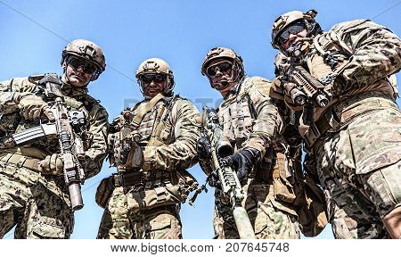 Half length low angle location shot of special forces soldiers in field uniforms with weapons, portrait on blue sky background