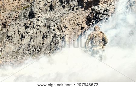 Special forces in action in the desert among the rocks covered by smoke screen