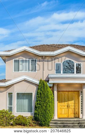 A perfect neighborhood. Houses in suburb at Summer in the north America. Fragment of a luxury house with nice window over blue sky.