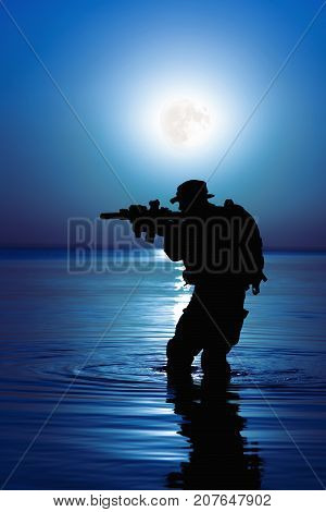 Army soldier with rifle night moon silhouette under cover of darkness in action during raid crossing river in the water. Covert diversionary operation