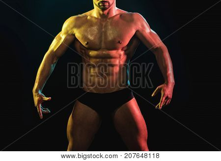 Strong bodybuilder with perfect abs shoulders biceps triceps chest. Handsome caucasian sexy fitness model in gym closeup abs concept man on diet shirtless training six pack healthcare lifestyle