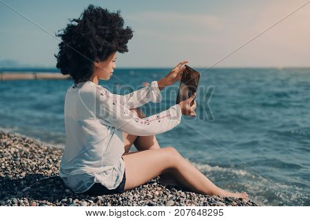Rear view of mixed girl with afro hair taking pictures of waterscape via digital pad; black young lady in wet chemise sitting on peeble shoreline and photographing sea water using her digital tablet
