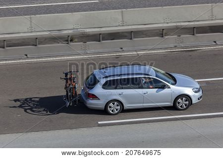 Frankfurt Germany - Sep 19 2017: Volkswagen Golf Variant with bicycles mounted on the tow-bar driving on the highway in Germany