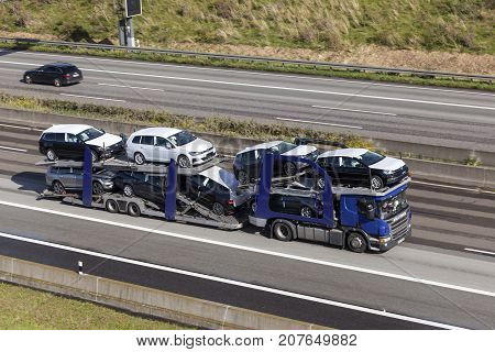 Frankfurt Germany - Sep 19 2017: Scania P410 car transporter hauls new Volkswagen Golf cars along the A45 highway in Germany