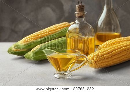 Glassware with corn oil on table against grey background