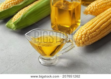 Glass gravy boat with corn oil on light background