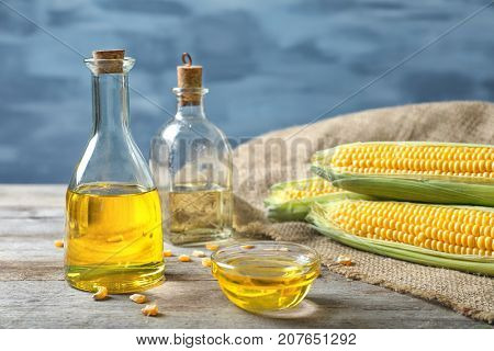 Glassware with corn oil on table against blurred background