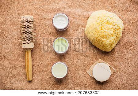 bodycare, beauty and spa concept - hair brush, body cream, sponge and soap bar on bath towel