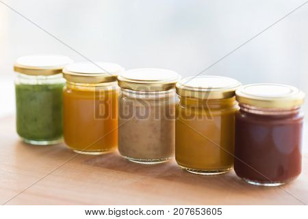 baby food, healthy eating and nutrition concept - vegetable or fruit puree or baby food in glass jars on wooden board