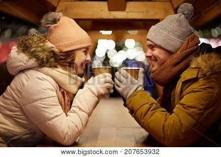 winter holidays, hot drinks and people concept - happy young couple with coffee at christmas market in evening