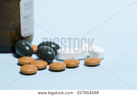 still life of pills over blue table with brown glass bottle. pharmaceutical. disease remedy