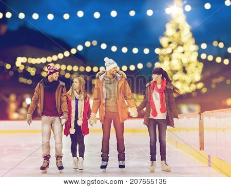 christmas, winter and leisure concept - happy friends holding hands on skating rink over outdoor holiday lights background poster