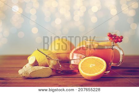 health, traditional medicine, folk remedy and ethnoscience concept - cup of tea with honey, lemon and ginger on wooden background