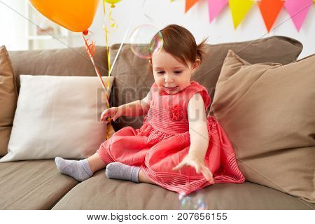 childhood, holidays and people concept - happy baby girl playing with soap bubbles on birthday party at home