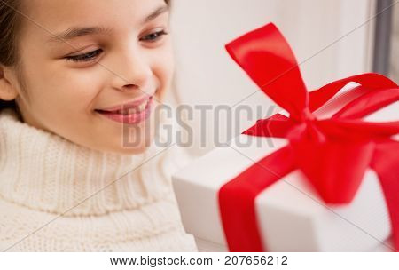 childhood, birthday, holidays and people concept - happy beautiful girl with christmas gift box at home