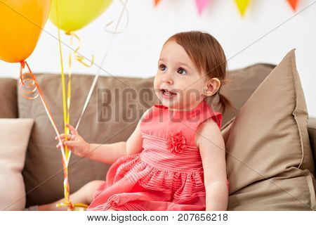 childhood, holidays and people concept - happy baby girl with air balloons on birthday party at home